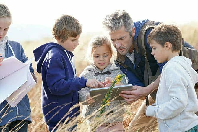 Erlebnispädagogik Ausbildung - Lehrer studiert Pflanzen und Blumen mit Kindern