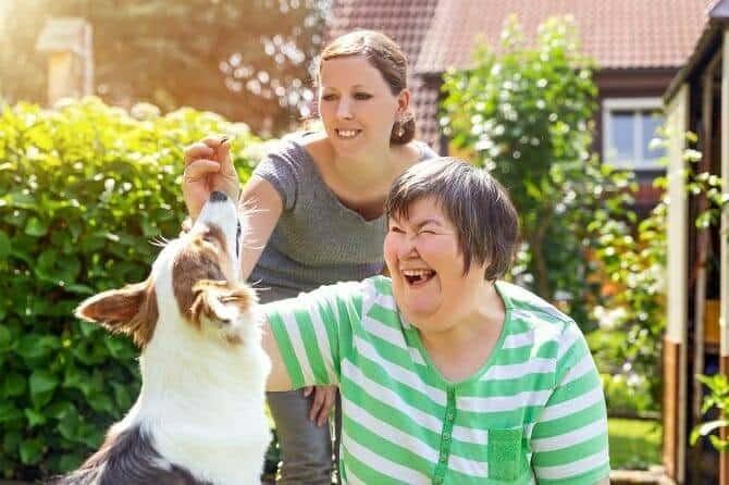 Assistenzhundetrainer Ausbildung - Geistig beeinträchtige Frau und Betreuerin spielen mit Hund