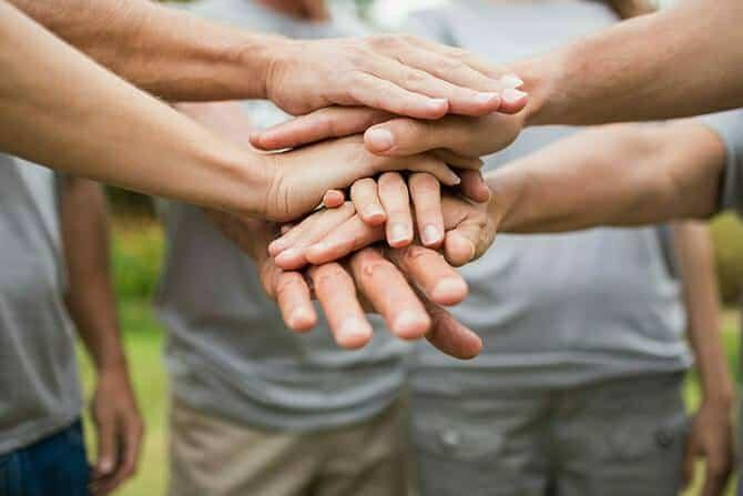 Erlebnispädagogik Ausbildung - Menschen legen Händ übreinandenr