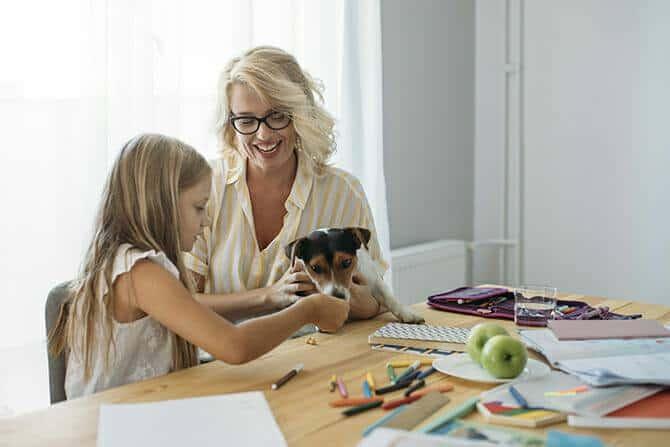 Therapiebegleithunde Trainer Ausbildung - lächelnde Mutter und Tochter spielen mit kleinem Hund während der Hausaufgaben