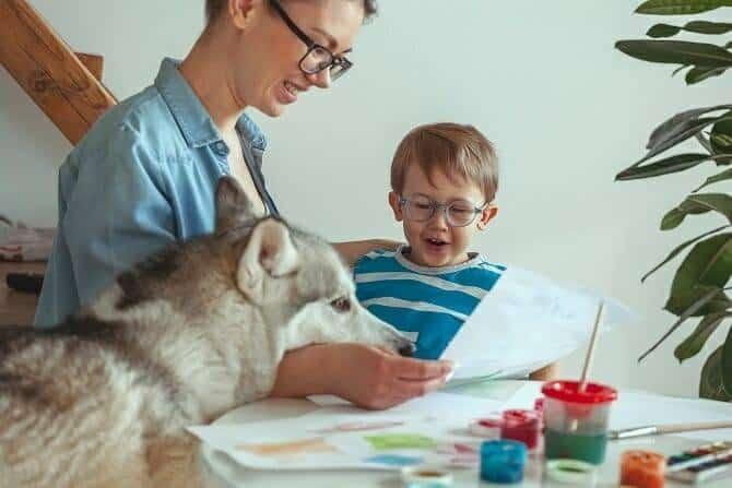 Therapiebegleithunde Trainer Ausbildung - Mutter und Sohn malen in Anwesenheit eines Hundes ein Bild