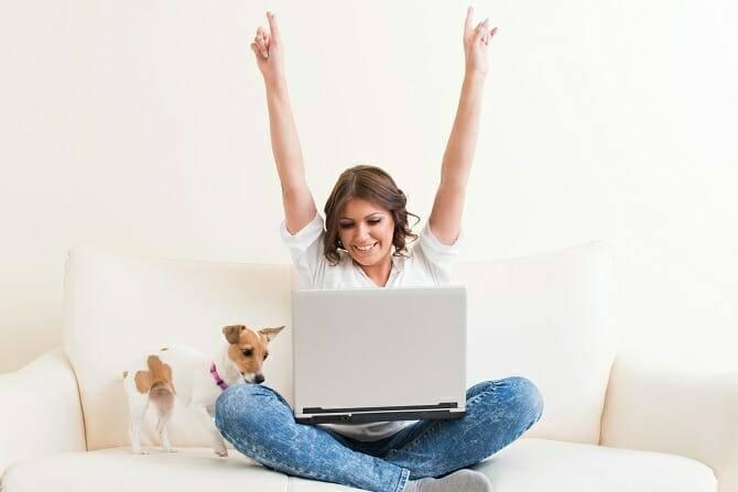 ATN Akademie - Junge Frau in Siegerpose vor Laptop mit Hund auf Couch