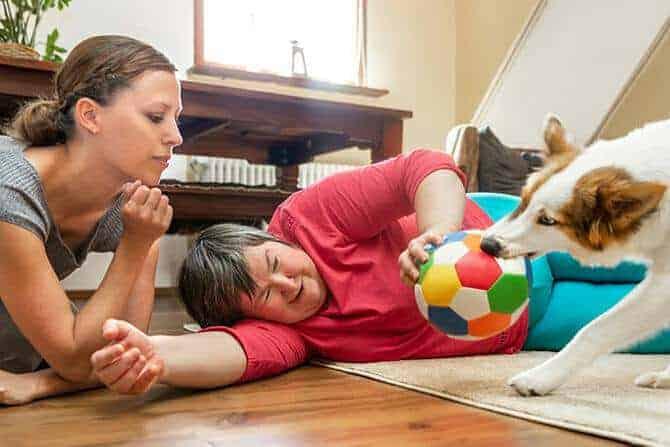 heilpraktiker fuer tiergestuetzte psychotherapie ausbildung geistig behinderte frau spielt ball mit hund betreuerin daneben