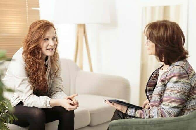 Heilpraktiker für Psychotherapie Ausbildung - Psychotherapeutin im Gespräch mit rothaariger Patientin