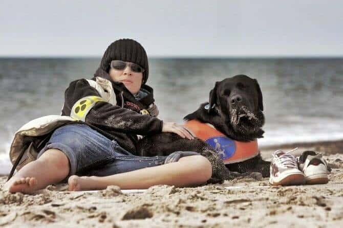 Assistenzhundetrainer Ausbildung - blinder junger Mann mit Assistenzhund am Strand