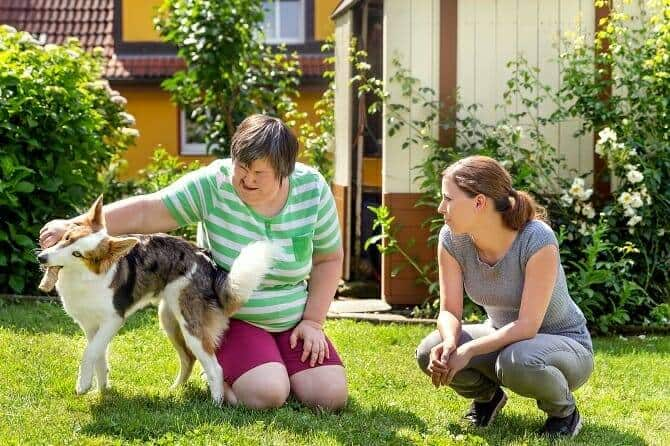 Assistenzhundetrainer Ausbildung - Geistig behinderte Frau mit Betreuerin und Hund im Garten