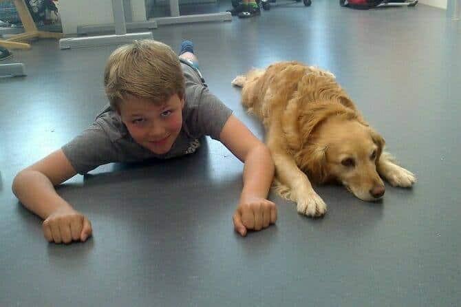 Assistenzhundetrainer Ausbildung - Junge liegt mit Hund auf dem Boden