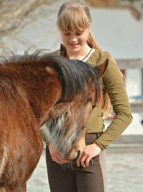 Pferdeverhaltensberater Ausbildung - Fohlen schnuppert an junger Frau