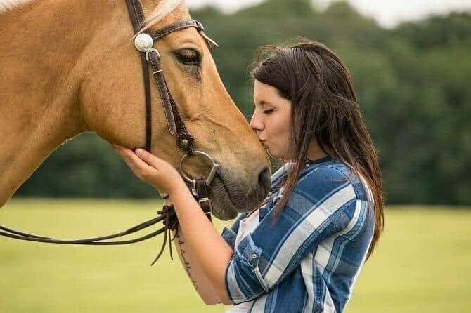 Pferdeverhaltensberater Ausbildung - Frau küsst Pferd mit Westerntrense auf den Kopf