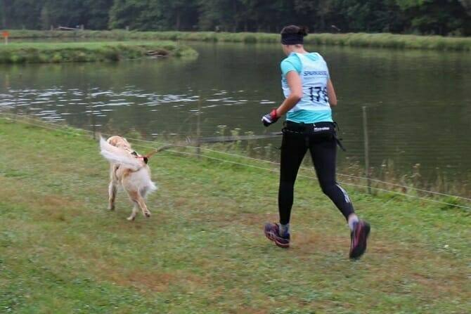 Sportwissenschaften Hund Ausbildung - Athletin mit Hund im Wettkampf laufend