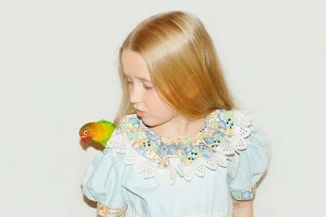 Tiergestützte Arbeit Ausbildung - blondes junges Mädchen mit einem Vogel auf der Schulter
