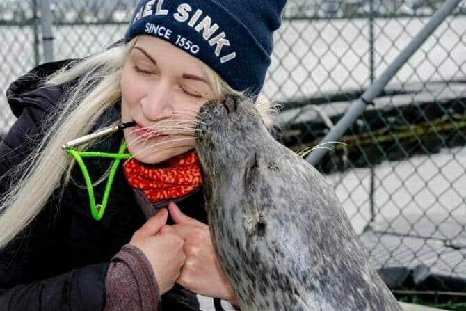 Tiertrainer Ausbildung - blonde Frau wird von Robbe geküsst